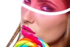 Όμορφη γυναίκα που τρώει το μεγάλο κόκκινο lollipop στο καπέλο ήλιων Στοκ Εικόνα