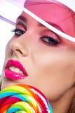 Όμορφη γυναίκα που τρώει το μεγάλο κόκκινο lollipop στο καπέλο ήλιων Στοκ Φωτογραφία