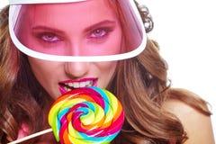 Όμορφη γυναίκα που τρώει το μεγάλο κόκκινο lollipop στο καπέλο ήλιων Στοκ Εικόνες