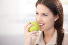 Όμορφη γυναίκα που τρώει το πράσινο χαμόγελο μήλων Στοκ Φωτογραφία