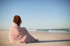 Όμορφη γυναίκα που τυλίγεται στη γενική συνεδρίαση στην παραλία στην ηλιοφάνεια στοκ εικόνες