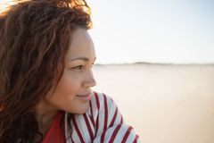 Όμορφη γυναίκα που τυλίγεται στο κάλυμμα που στέκεται στην παραλία στην ηλιοφάνεια στοκ φωτογραφία