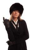 Όμορφη γυναίκα που φορά ένα καπέλο γουνών, έναν μαύρους δεσμό και γάντια δέρματος Στοκ Φωτογραφίες