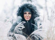 Όμορφη γυναίκα που φορά ένα χειμερινό παλτό κουκουλών γουνών στοκ εικόνες