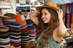 Όμορφη γυναίκα που φορά ένα χειροποίητο καπέλο του Παναμά στην αγορά τεχνών σε Otavalo, Ισημερινός, ζωηρόχρωμο υπόβαθρο υφασμάτων Στοκ φωτογραφία με δικαίωμα ελεύθερης χρήσης
