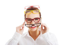 Όμορφη γυναίκα που φορά τέσσερα διαφορετικά ζευγάρια eyeglasses. Στοκ Φωτογραφία