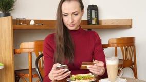 Όμορφη γυναίκα που φορά τις κόκκινες σε απευθείας σύνδεση τραπεζικές εργασίες φορεμάτων που πληρώνουν χρησιμοποιώντας το smartpho φιλμ μικρού μήκους