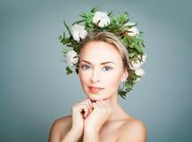 Όμορφη γυναίκα που φορά το στεφάνι λουλουδιών στο μπλε υπόβαθρο εμβλημάτων Στοκ εικόνα με δικαίωμα ελεύθερης χρήσης