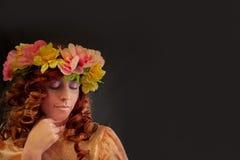 Όμορφη γυναίκα που φορά το στεφάνι των όμορφων λουλουδιών Στοκ Εικόνα