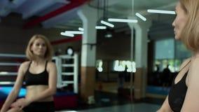 Όμορφη γυναίκα που φορά sportswear που τεντώνει το σώμα της μπροστά από τον καθρέφτη στη γυμναστική απόθεμα βίντεο