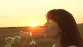 Όμορφη γυναίκα που φυσά τις διαφανείς φυσαλίδες και το χαμόγελο σαπουνιών o παιχνίδι νέων κοριτσιών στο πάρκο και φύσηγμα απόθεμα βίντεο