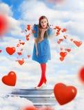 Όμορφη γυναίκα που φυσά τις κόκκινες καρδιές από τον ουρανό Στοκ Εικόνες