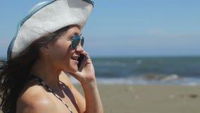 Όμορφη γυναίκα που χαμογελά, αριθμός σχηματισμού, μιλώντας στο τηλέφωνο, που τελειώνει την κλήση στην παραλία απόθεμα βίντεο