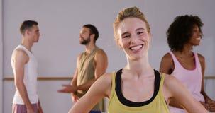 Όμορφη γυναίκα που χαμογελά ενώ η ομάδα της που μιλά στο υπόβαθρο στο στούντιο ικανότητας φιλμ μικρού μήκους