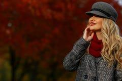 Όμορφη γυναίκα που χαμογελά στο πάρκο φθινοπώρου Κόκκινο υπόβαθρο κήπων σφενδάμνου κοίταγμα αριστερά του πλαισίου προς το κενό δι Στοκ φωτογραφίες με δικαίωμα ελεύθερης χρήσης