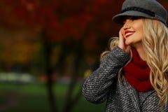 Όμορφη γυναίκα που χαμογελά στο πάρκο φθινοπώρου Κόκκινο υπόβαθρο κήπων σφενδάμνου κοίταγμα αριστερά του πλαισίου προς το κενό δι Στοκ εικόνα με δικαίωμα ελεύθερης χρήσης