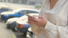 Όμορφη γυναίκα που χρησιμοποιεί την έξυπνη τηλεφωνική τεχνολογία app στον αστικό ευτυχή τρόπο ζωής διαβίωσης οδών πόλεων o φιλμ μικρού μήκους