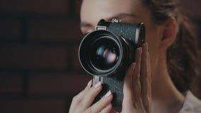 Όμορφη γυναίκα που χρησιμοποιεί την αναδρομική κάμερα φωτογραφιών Φωτογράφος κοριτσιών που εργάζεται στο στούντιο απόθεμα βίντεο