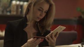 Όμορφη γυναίκα που χρησιμοποιεί την πλαστική τραπεζική κάρτα και το κινητό τηλέφωνο για on-line να ψωνίσει απόθεμα βίντεο