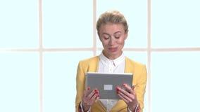 Όμορφη γυναίκα που χρησιμοποιεί την ταμπλέτα PC στο χώρο εργασίας απόθεμα βίντεο