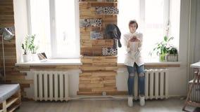 Όμορφη γυναίκα που χρησιμοποιεί το κινητό τηλέφωνο που στέκεται το μπροστινό παράθυρο στο δωμάτιο απόθεμα βίντεο