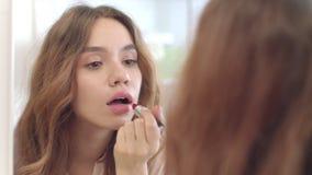 Όμορφη γυναίκα που χρησιμοποιεί το κραγιόν για καθρέφτη χειλικών makeup τον μπροστινό λουτρών στο σπίτι απόθεμα βίντεο