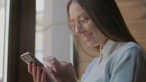 Όμορφη γυναίκα που χρησιμοποιεί app στο smartphone στον καφέ απόθεμα βίντεο