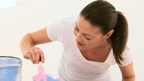Όμορφη γυναίκα που χρωματίζει έναν τοίχο φιλμ μικρού μήκους