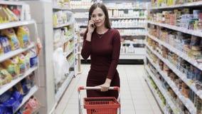 Όμορφη γυναίκα που ψωνίζει στην υπεραγορά και που μιλά στο τηλέφωνο, steadicam πυροβολισμός απόθεμα βίντεο