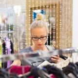Όμορφη γυναίκα που ψωνίζει στο κατάστημα ιματισμού Στοκ Εικόνες