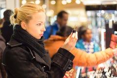 Όμορφη γυναίκα που ψωνίζει στο κατάστημα ομορφιάς Στοκ Φωτογραφίες