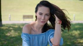 Όμορφη γυναίκα, πρότυπο μόδας με τη μακροχρόνια καφετιά συνεδρίαση τρίχας στην πράσινη χλόη απόθεμα βίντεο