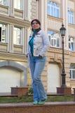 Όμορφη γυναίκα σε ένα άσπρο σακάκι σε ένα υπόβαθρο ενός σπιτιού στοκ εικόνες