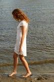 Όμορφη γυναίκα σε ένα άσπρο φόρεμα στην ακτή Στοκ Εικόνες
