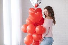 Όμορφη γυναίκα σε ένα γκρίζο υπόβαθρο με μια δέσμη των κόκκινων μπαλονιών με μορφή μιας καρδιάς Στοκ Φωτογραφία