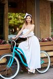 Όμορφη γυναίκα σε ένα εκλεκτής ποιότητας ποδήλατο κοντά στον καφέ θερινών οδών στοκ φωτογραφία
