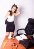Όμορφη γυναίκα σε ένα επιχειρησιακό κοστούμι που στέκεται σε ένα γραφείο με τον υπολογιστή η γυναίκα πίνει τον καφέ από ένα άσπρο Στοκ φωτογραφίες με δικαίωμα ελεύθερης χρήσης