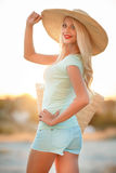 Όμορφη γυναίκα σε ένα καπέλο αχύρου στο ηλιοβασίλεμα στοκ φωτογραφία