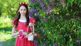 Όμορφη γυναίκα σε ένα κόκκινο φόρεμα με ένα στεφάνι και ένα καλάθι με τις τουλίπες απόθεμα βίντεο