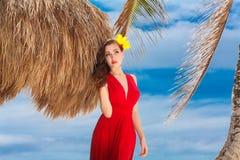 Όμορφη γυναίκα σε ένα κόκκινο φόρεμα στην τροπική παραλία Στοκ Φωτογραφία