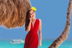 Όμορφη γυναίκα σε ένα κόκκινο φόρεμα στην τροπική παραλία Στοκ Εικόνα