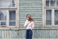 Όμορφη γυναίκα σε ένα πλεκτό πουλόβερ στο υπόβαθρο του παλαιού woode Στοκ Εικόνα
