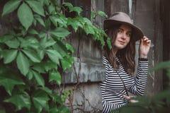 Όμορφη γυναίκα σε ένα ριγωτό πουκάμισο που κρατά το καπέλο της και που εξετάζει μια κάμερα στοκ φωτογραφίες με δικαίωμα ελεύθερης χρήσης