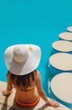 Όμορφη γυναίκα σε μια άσπρη συνεδρίαση καπέλων Στοκ Εικόνες