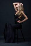 Όμορφη γυναίκα σε μια μαύρη τοποθέτηση φορεμάτων βραδιού με την καρέκλα Στοκ φωτογραφία με δικαίωμα ελεύθερης χρήσης