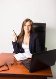 Όμορφη γυναίκα σε μια συνεδρίαση επιχειρησιακών κοστουμιών σε ένα γραφείο με τον υπολογιστή Στοκ φωτογραφίες με δικαίωμα ελεύθερης χρήσης