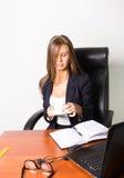 Όμορφη γυναίκα σε μια συνεδρίαση επιχειρησιακών κοστουμιών σε ένα γραφείο με τον υπολογιστή η γυναίκα πίνει τον καφέ από ένα άσπρ Στοκ φωτογραφία με δικαίωμα ελεύθερης χρήσης