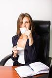 Όμορφη γυναίκα σε μια συνεδρίαση επιχειρησιακών κοστουμιών σε ένα γραφείο με τον υπολογιστή η γυναίκα πίνει τον καφέ από ένα άσπρ Στοκ Εικόνα