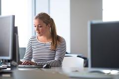 Όμορφη, γυναίκα σπουδαστής που εξετάζει έναν υπολογιστή γραφείου Στοκ Εικόνες