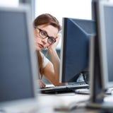 Όμορφη, γυναίκα σπουδαστής που εξετάζει μια οθόνη υπολογιστή υπολογιστών γραφείου Στοκ φωτογραφίες με δικαίωμα ελεύθερης χρήσης